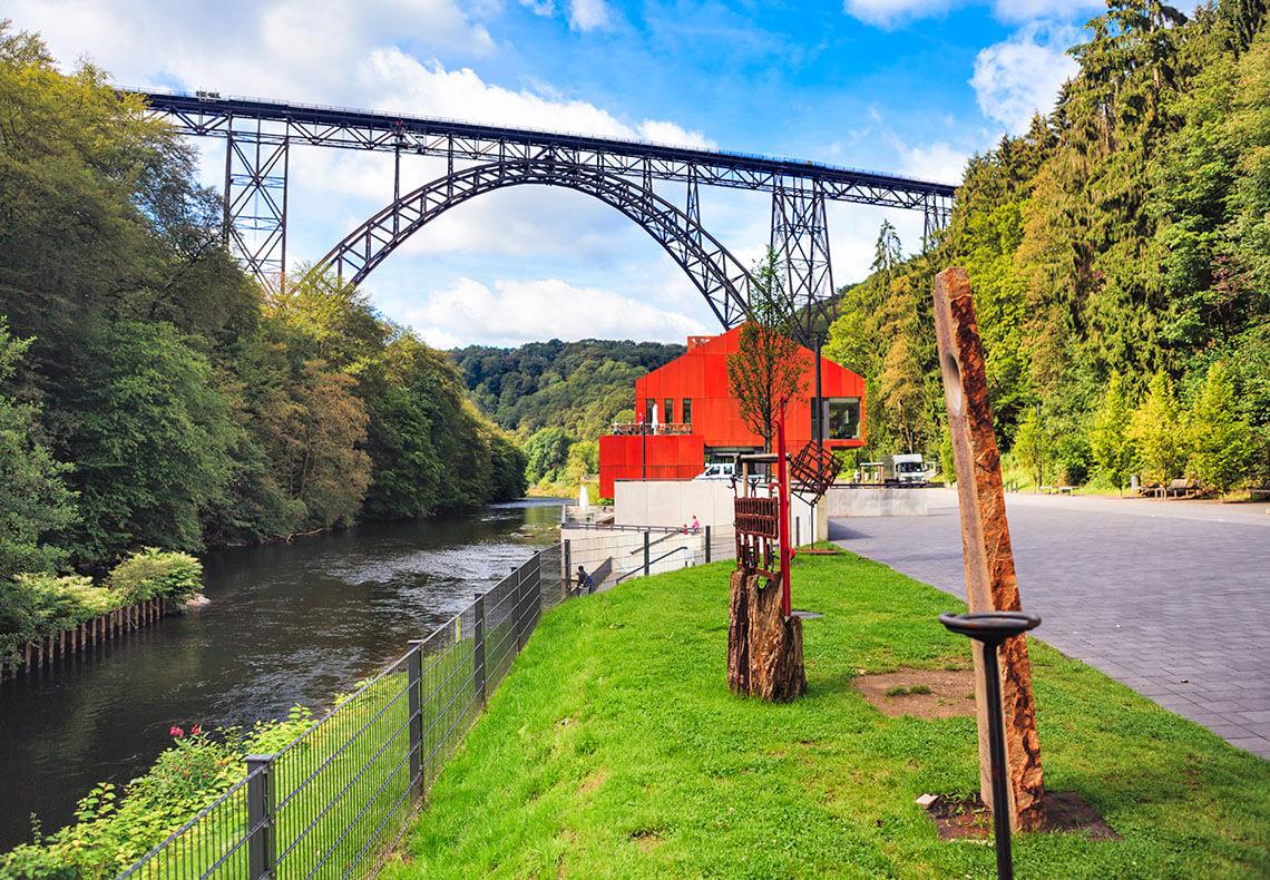 Ein Haus neben einem Fluss unter einer Radbrücke.