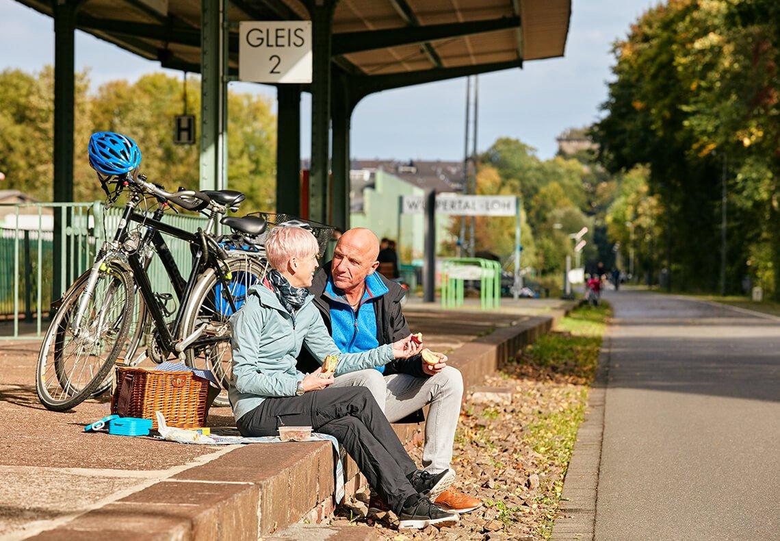 Mann und Frau picknicken an einem Radweg.