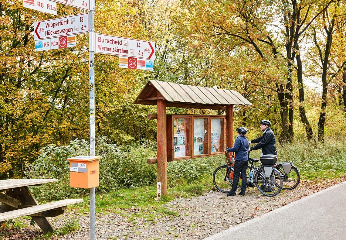 Zwei Radfahrer schauen auf eine Karte.