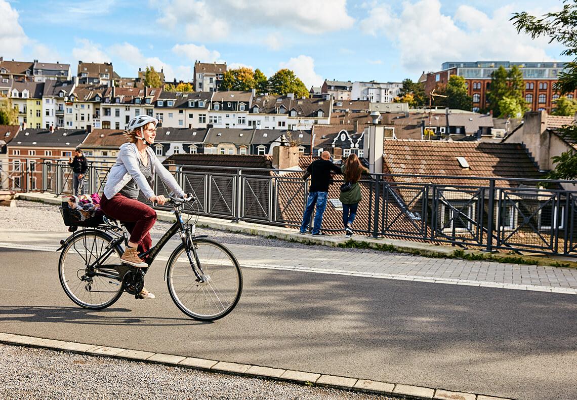 Eine Frau fährt auf einem Fahrrad über ein Viadukt mit Aussicht auf Wuppertal.