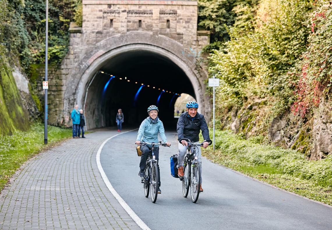 Zwei Radfahrer fahren durch einen Tunnel.